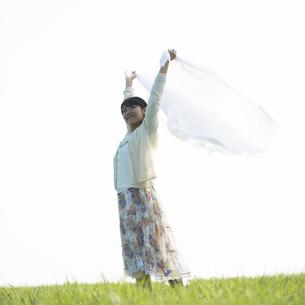 草原で布を持ち微笑む女性の写真素材 [FYI04556498]