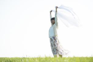 草原で布を持ち微笑む女性の写真素材 [FYI04556503]
