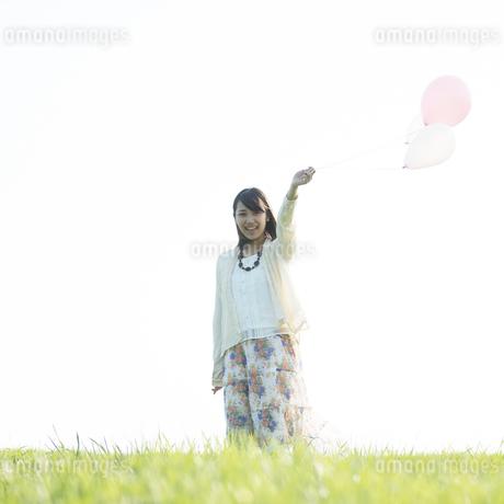 草原で風船を持ち微笑む女性の写真素材 [FYI04556507]