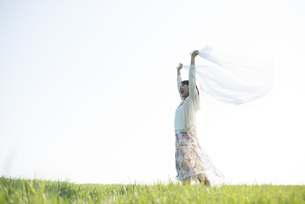 草原で布を持ち微笑む女性の写真素材 [FYI04556509]