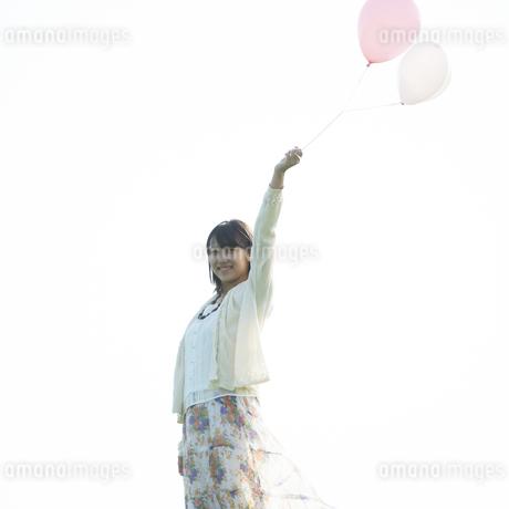 風船を持ち微笑む女性の写真素材 [FYI04556513]