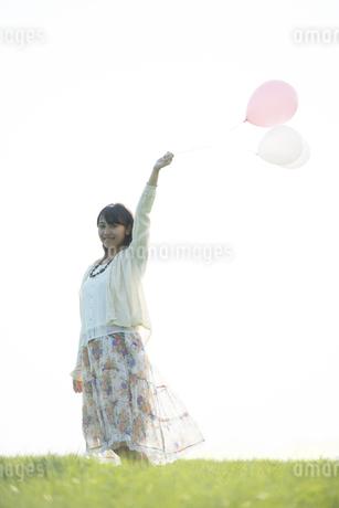 草原で風船を持ち微笑む女性の写真素材 [FYI04556515]