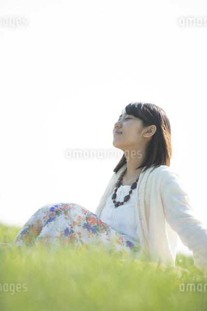 草原で目を閉じる女性の写真素材 [FYI04556517]