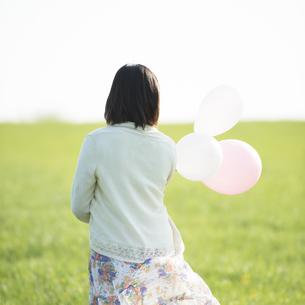 草原で風船を持つ女性の後姿の写真素材 [FYI04556518]