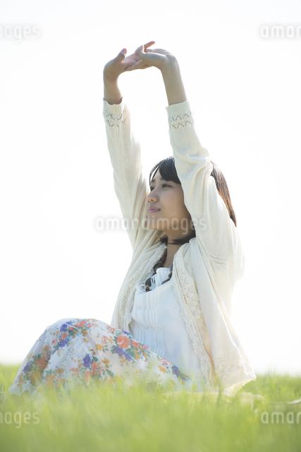 草原で深呼吸をする女性の写真素材 [FYI04556524]