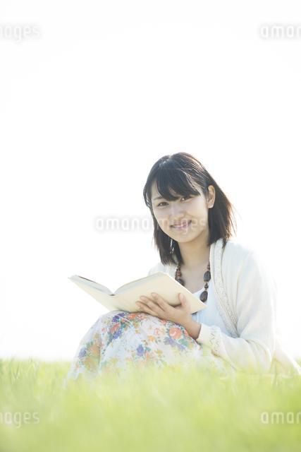 草原で本を読む女性の写真素材 [FYI04556525]