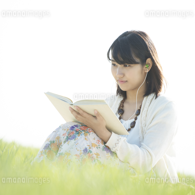 草原で音楽を聴きながら本を読む女性の写真素材 [FYI04556529]