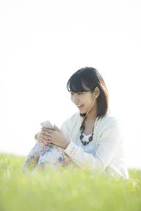 草原で音楽を聴く女性の写真素材 [FYI04556533]
