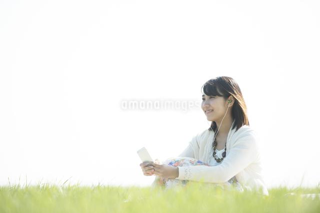 草原で音楽を聴く女性の写真素材 [FYI04556542]