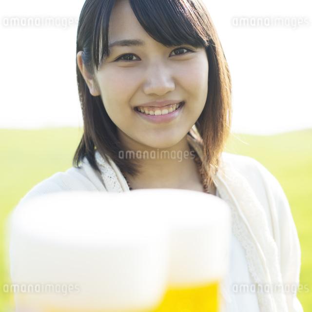 ビールを持ち微笑む女性の写真素材 [FYI04556557]