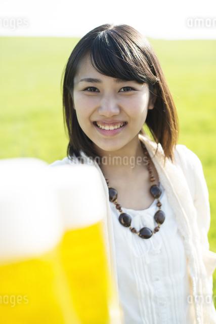 ビールを持ち微笑む女性の写真素材 [FYI04556562]