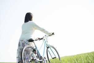 草原で自転車を押す女性の後姿の写真素材 [FYI04556581]