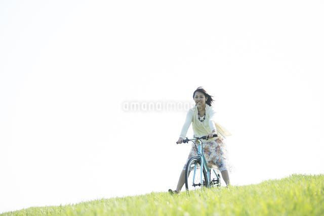 草原で自転車に乗る女性の写真素材 [FYI04556583]