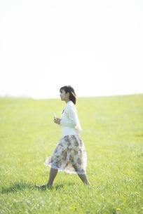 草原で音楽を聴く女性の写真素材 [FYI04556601]