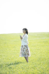 草原で音楽を聴く女性の写真素材 [FYI04556603]