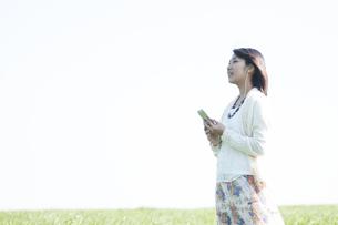 草原で音楽を聴く女性の写真素材 [FYI04556610]