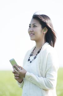 草原で音楽を聴く女性の写真素材 [FYI04556612]