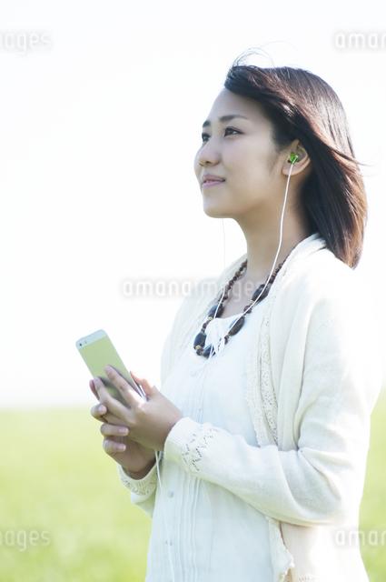 草原で音楽を聴く女性の写真素材 [FYI04556614]