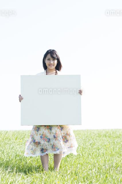 草原でメッセージボードを持ち微笑む女性の写真素材 [FYI04556616]