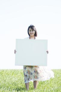 草原でメッセージボードを持ち微笑む女性の写真素材 [FYI04556621]