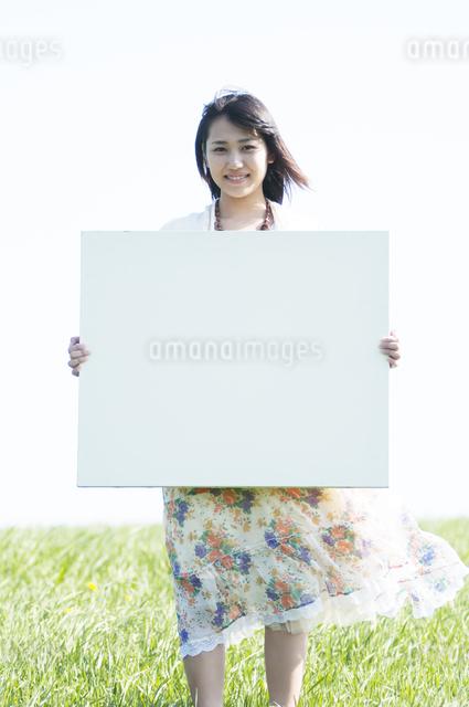 草原でメッセージボードを持ち微笑む女性の写真素材 [FYI04556623]