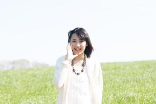 口元に手をあて微笑む女性の写真素材 [FYI04556628]