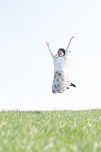 草原でジャンプをする女性の写真素材 [FYI04556662]