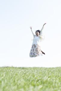 草原でジャンプをする女性の写真素材 [FYI04556663]