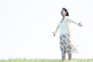 草原で深呼吸をする女性の写真素材 [FYI04556668]