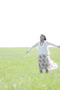 草原で深呼吸をする女性の写真素材 [FYI04556674]