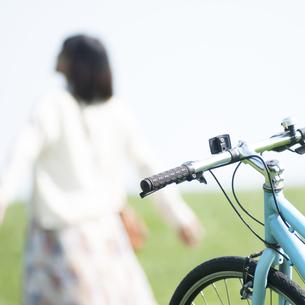 自転車と草原で深呼吸をする女性の写真素材 [FYI04556678]