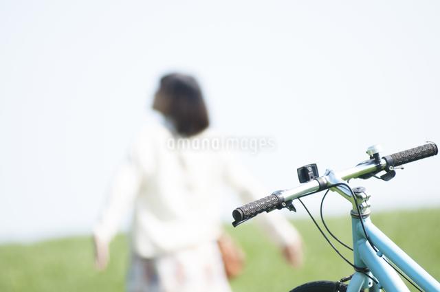 自転車と草原で深呼吸をする女性の写真素材 [FYI04556679]