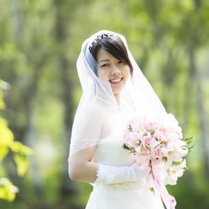 ブーケを持ち微笑む花嫁の写真素材 [FYI04556705]