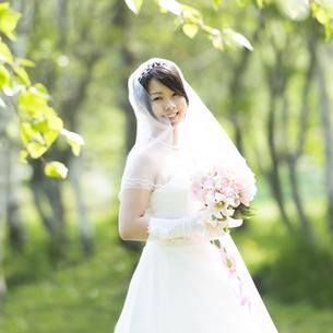 ブーケを持ち微笑む花嫁の写真素材 [FYI04556712]