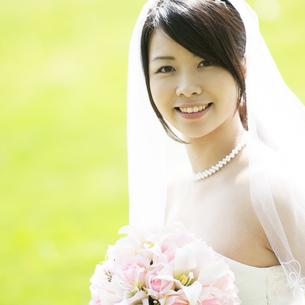 ブーケを持ち微笑む花嫁の写真素材 [FYI04556718]