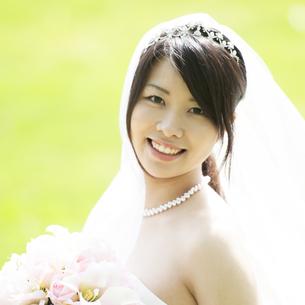 ブーケを持ち微笑む花嫁の写真素材 [FYI04556724]