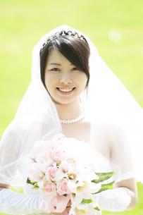ブーケを持ち微笑む花嫁の写真素材 [FYI04556727]