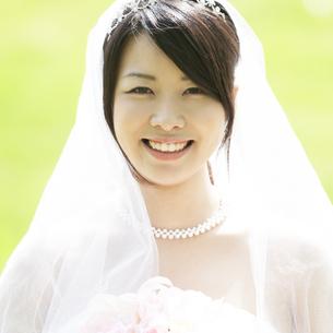 ブーケを持ち微笑む花嫁の写真素材 [FYI04556728]