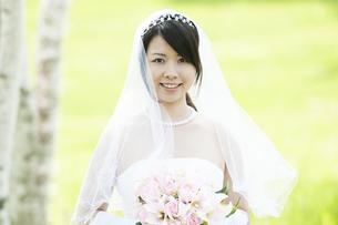ブーケを持ち微笑む花嫁の写真素材 [FYI04556737]