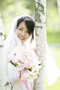 ブーケを持ち微笑む花嫁の写真素材 [FYI04556738]