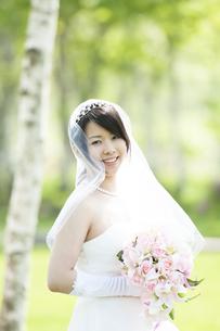 ブーケを持ち微笑む花嫁の写真素材 [FYI04556740]
