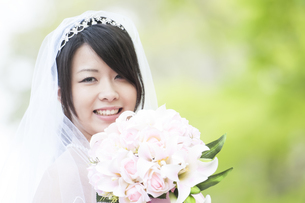 新緑の中でブーケを持ち微笑む花嫁の写真素材 [FYI04556745]