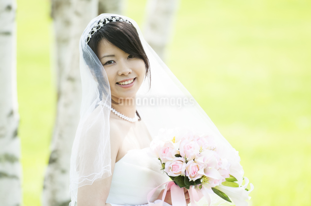 ブーケを持ち微笑む花嫁の写真素材 [FYI04556747]