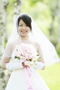 ブーケを持ち微笑む花嫁の写真素材 [FYI04556748]
