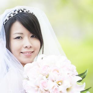 新緑の中でブーケを持ち微笑む花嫁の写真素材 [FYI04556749]