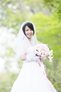 新緑の中でブーケを持ち微笑む花嫁の写真素材 [FYI04556750]