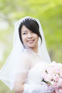新緑の中でブーケを持ち微笑む花嫁の写真素材 [FYI04556753]