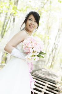 新緑の中でブーケを持ち微笑む花嫁の写真素材 [FYI04556754]