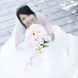 ブーケを持ち微笑む花嫁の写真素材 [FYI04556756]