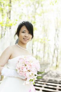 新緑の中でブーケを持ち微笑む花嫁の写真素材 [FYI04556757]